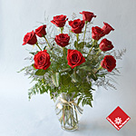 A dozen beautiful red roses in a vase.