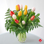 Colorful spring tulips in a clear glass vase.