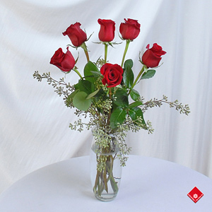 Six roses in a glass vase.