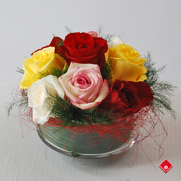 Assorted roses in a glass dish.