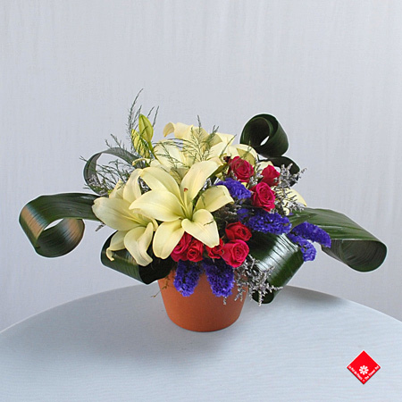 Fresh flower arrangement of lilies in a clay pot.