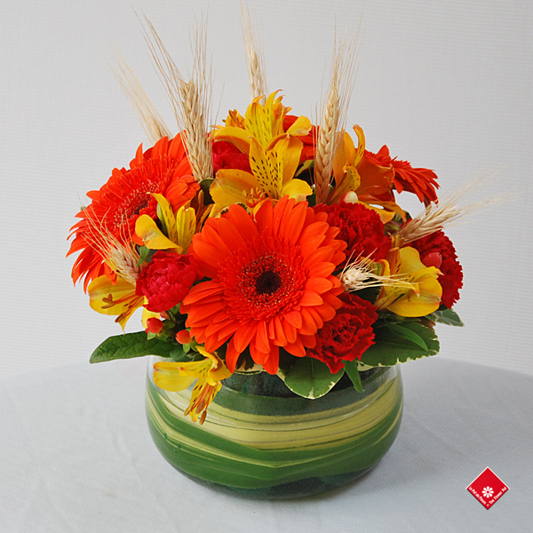 Fall flower arrangements of colorful blooms and  wheat.