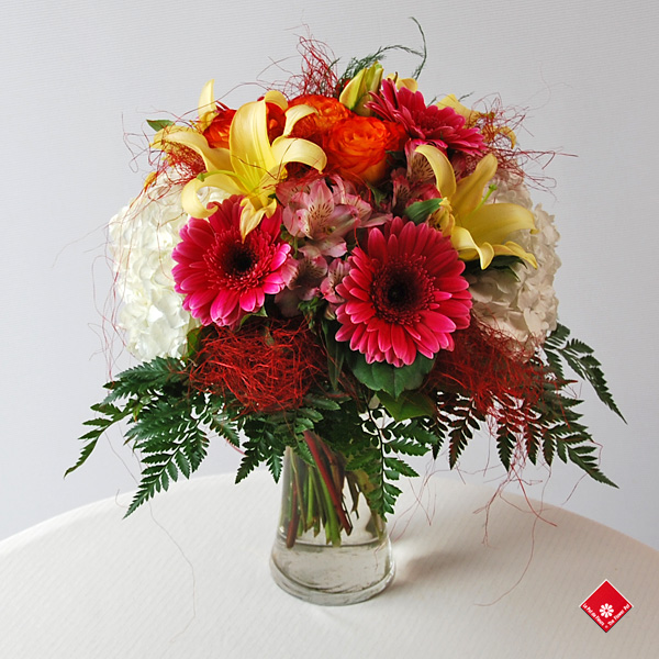 Hand tied bouquet of assorted flowers in vase.