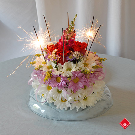 Birthday flower cake made of daisies, roses, and glowing sparklers.