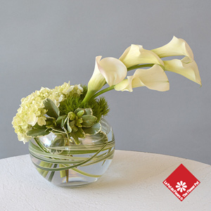 Mini calla lilies and more in glass bowl.