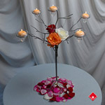 Votive candle holders decorated with fresh roses and rose petals.
