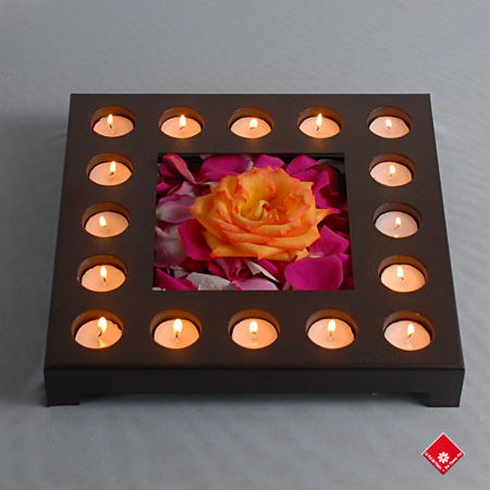 Candle centerpiece with fresh rose and rose petals.