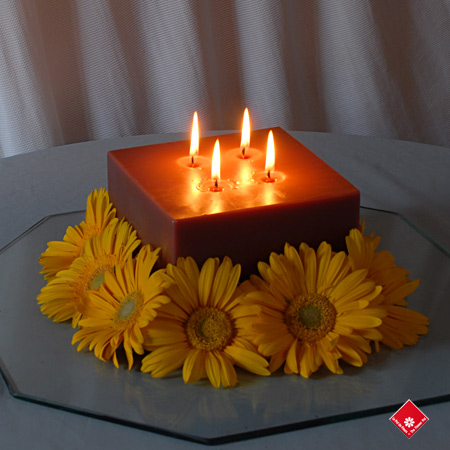 Large candle with four wicks and fresh gerberas.