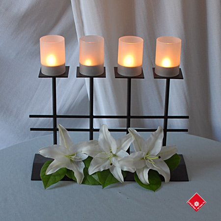 Modern candle holder with fresh white lilies.