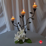 Iron and glass candle holder with fresh white lilies.