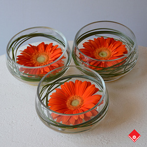 Here's an effective but thrifty money-saving idea for a dinner table décor: floating colourful flowers in matching short vases.