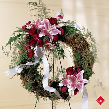 Sympathy wreath of lilies, roses, carnations, and greenery.