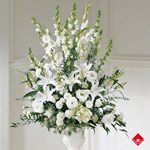 Funeral flower arrangement of lilies, gladiola, snapdragon, and carnations.