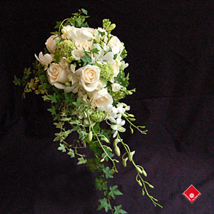 Cascading bridal bouquet of white roses, orchids, and freesias.