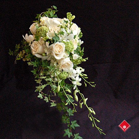 Cascading bridal bouquet of white roses, orchids, and freesias - The Flower Pot