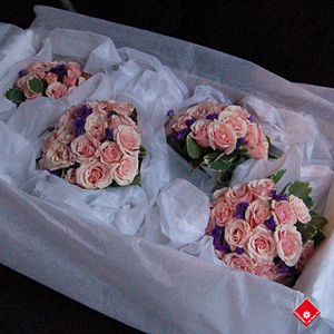 Bridesmaid flowers of roses, statice, and pittosporum.