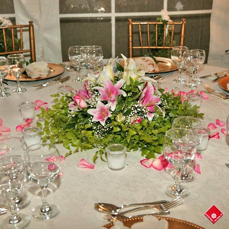 Lilies and scattered rose petals for wedding reception flowers.