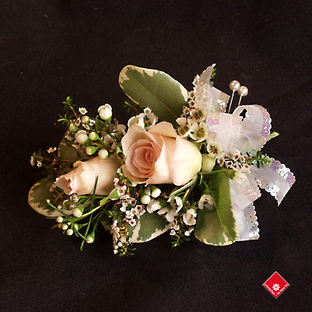 Feminine corsage made of mini roses for a Montreal wedding .