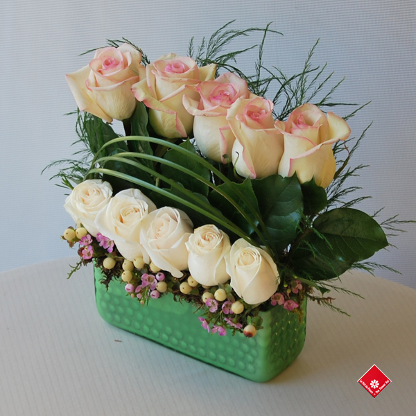 Ten roses in a green glass container.