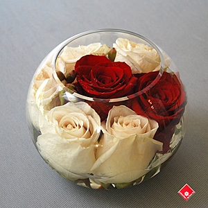 Roses in a clear glass rose bowl.