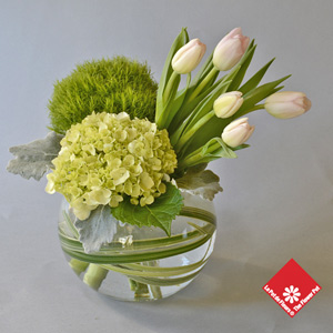 Tulips and more in glass bowl.