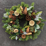 Traditional wreath with pinecones and red decorative ribbon.